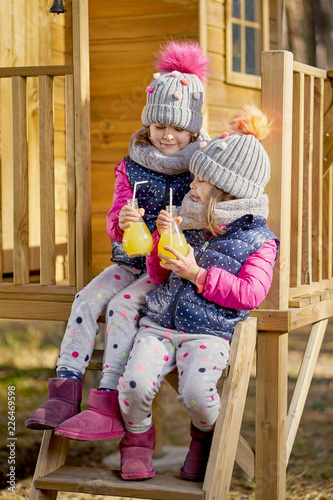 Fotografia  two little girls in a cap and jacket are drinking lemonade in a house in an autu