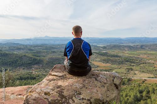 Fotografía  Man sitter på på bergstopp och tittar på utsikten över dalen