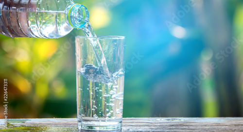 Fotomural  Drink water pouring in to glass over sunlight and natural green background