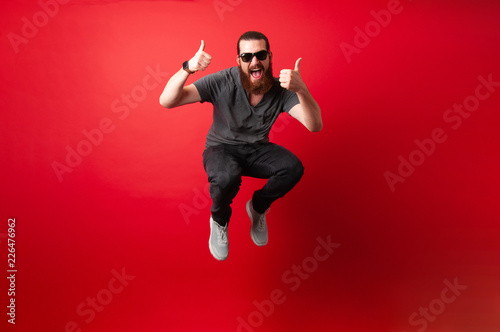 Fotografia Cheerful bearded hipster man with sunglasses jump over red background and showin