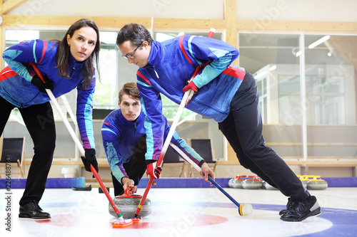 Fotografiet Curling. Zawodnicy grają w curling na torze curlingowym.