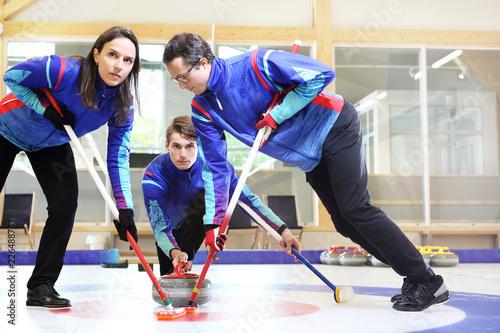 Curling. Zawodnicy grają w curling na torze curlingowym. Fototapete