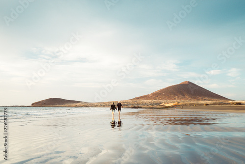 In de dag Canarische Eilanden El Médano, Tenerife, Canary Islands, Spain - September 28, 2018: an older couple walking through El Médano beach, in south of Tenerife island