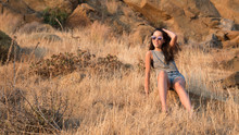 Teen Sitting In Dry Brush On The Side Of A Mountain With Sun Purple Glasses