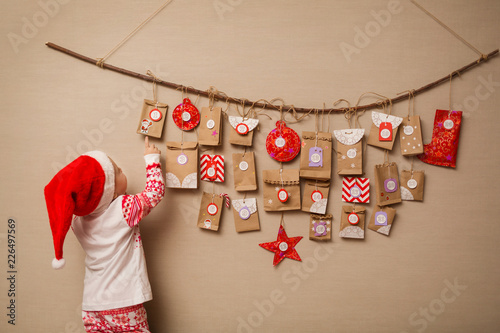 Fototapeta child looks at the advent calendar. Baby girl in a Christmas hat and pajamas shows on first gift obraz