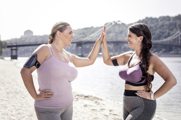 Productive workout. Cheerful positive women giving high five to each other while standing on the beach after the workout