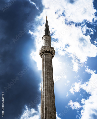Fotografia  Minaret of an Islamic mosque photographed from below against a dramatic sky with clouds