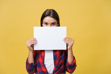 Banner Sign Woman Peeking Over Edge Of Blank Empty Paper With Copy Space For Text. Beautiful Caucasian Woman Looking Surprised And Scared - Funny. Isolated On Yellow Background.
