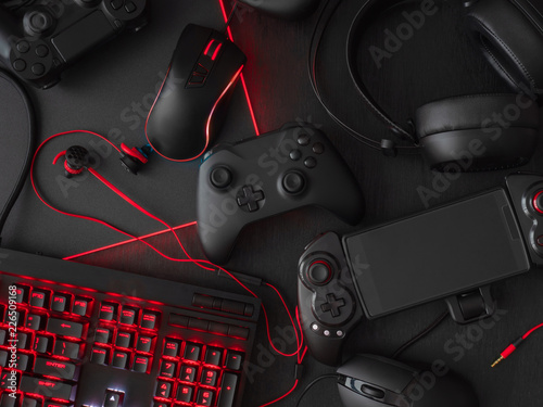 Fotografie, Tablou  gamer workspace concept, top view a gaming gear, mouse, keyboard, joystick, headset, mobile joystick, in ear headphone and mouse pad on black table background