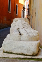 The Marble Foot Of A Colossal Roman Statue In An Alley In Rome, Italy