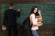 canvas print picture - She has got books she needs. Woman student look in glasses with book stack and backpack with teacher man writing on chalkboard at school. Preparation to exam. Confident in knowledge. I love to study