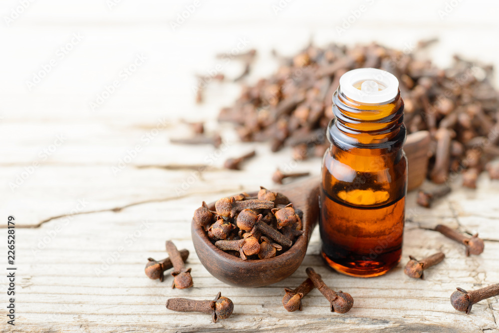 Fototapety, obrazy: clove essential oil in the glass bottle, on the wooden board