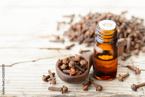 clove essential oil in the glass bottle, on the wooden board Fototapete