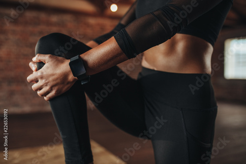 Fotografiet  Woman doing stretching workout at gym