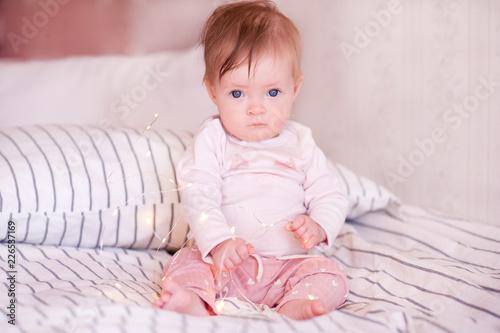 Cute Baby Girl Wake Up In Bed Wearing Pajamas Closeup Looking At