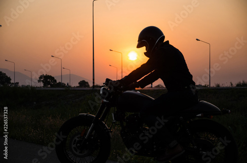 silhouette of man riding vintage motorcycle cafe racer style with helmet on suns Fototapeta