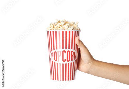 Woman holding cup with delicious popcorn on white background, closeup