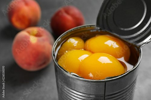 Tin can with conserved peach halves on table, closeup