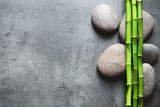 Flat lay composition with green bamboo stems on grey background. Space for text