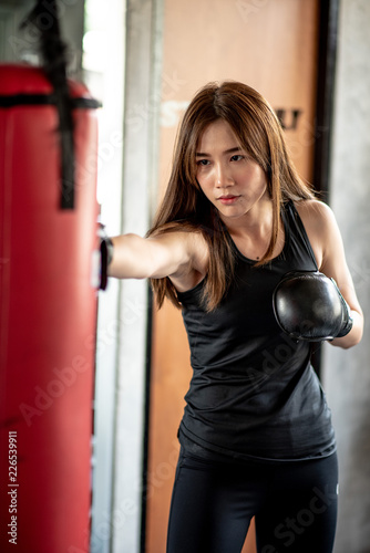 Pinturas sobre lienzo  Attractive female boxer training with kick boxing at gym with blackgloves