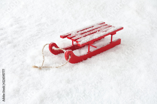 Obraz Red Wooden Sledge in Snow covered with Snowflakes - fototapety do salonu