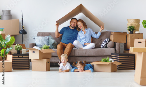 Fototapeta happy family mother father and children move to new apartment and unpack boxes obraz
