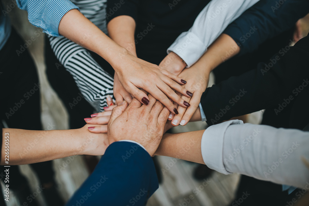 Fototapeta Group of business people team joining hands together in office.