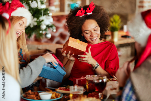 Fotografía  Friends giving gifts to each other while sitting at table