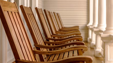Wooden Rocking Chairs In A Row On A Veranda With Blurred Background
