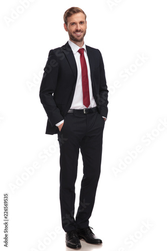 Papel de parede relaxed businessman smiling and standing with hands in pockets