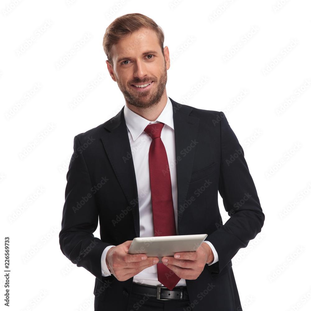 Fototapeta portrait of smiling unshaved businessman holing a tablet