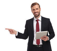 Smiling Businessman With Pad Pointing Finger To Side