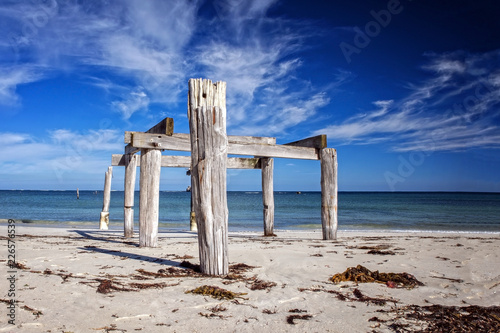 Foto op Aluminium Oceanië Old ruinous jetty with wooden timber at a sunny morning light at a deserted beach as wide-angle panorama