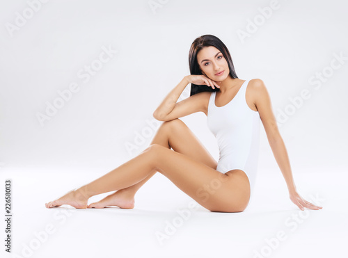 Obraz Fit and sporty girl in white swimsuit. Sport, fitness, diet, weight loss and healthcare concept. - fototapety do salonu