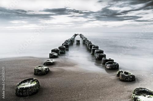 Fototapeta bezkresne morze i stary drewniany falochron obraz