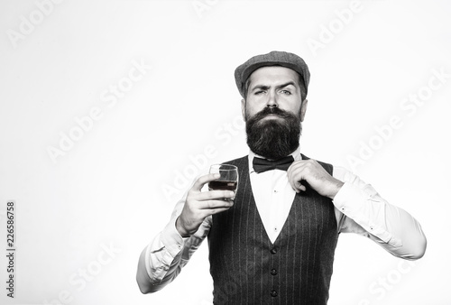 Bearded in is holding a glass of whiskey. Sommelier tastes expensive drink. Handsome well-dressed man in jacket with glass of beverage. Bearded man wearing suit and drinking whiskey, brandy, cognac.