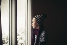 Thoughtful Teenage Boy Looking Through Window At Home