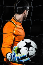 Side View Of Goalie Holding Soccer Ball While Standing By Net Against Black Background