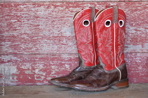 Photo red cowboy boots on red barn board
