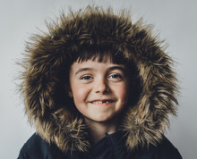 Portrait Of Boy In Fur Coat Standing Against White Background