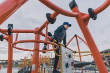 Boy Climbing Jungle Gym At Pla...