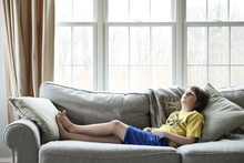 Full Length Of Thoughtful Boy Lying On Sofa In Living Room At Home