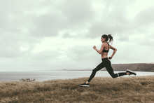 Woman Running On Grassy Field ...