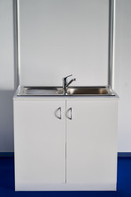 White Cabinet Kitchen Sink With Chrome Water Tap Against White Wall Background.