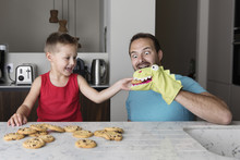 Playful Son Feeding Chocolate Chip Cookie To Puppet Worn By Father