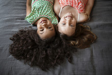 Portrait Of Two Girls Lying On Bed At Home