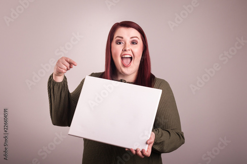 Obraz Woman holding a blank board pointing a finger at blank sign excited happy facial expression - fototapety do salonu