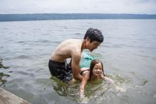 Father Teaching Daughter Wearing Mermaid Costume To Swim In Lake