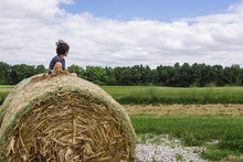Boy Sitting On Hay Bale Agains...