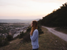 Side View Of Woman Looking Away While Standing On Mountain Against Sky During Sunset